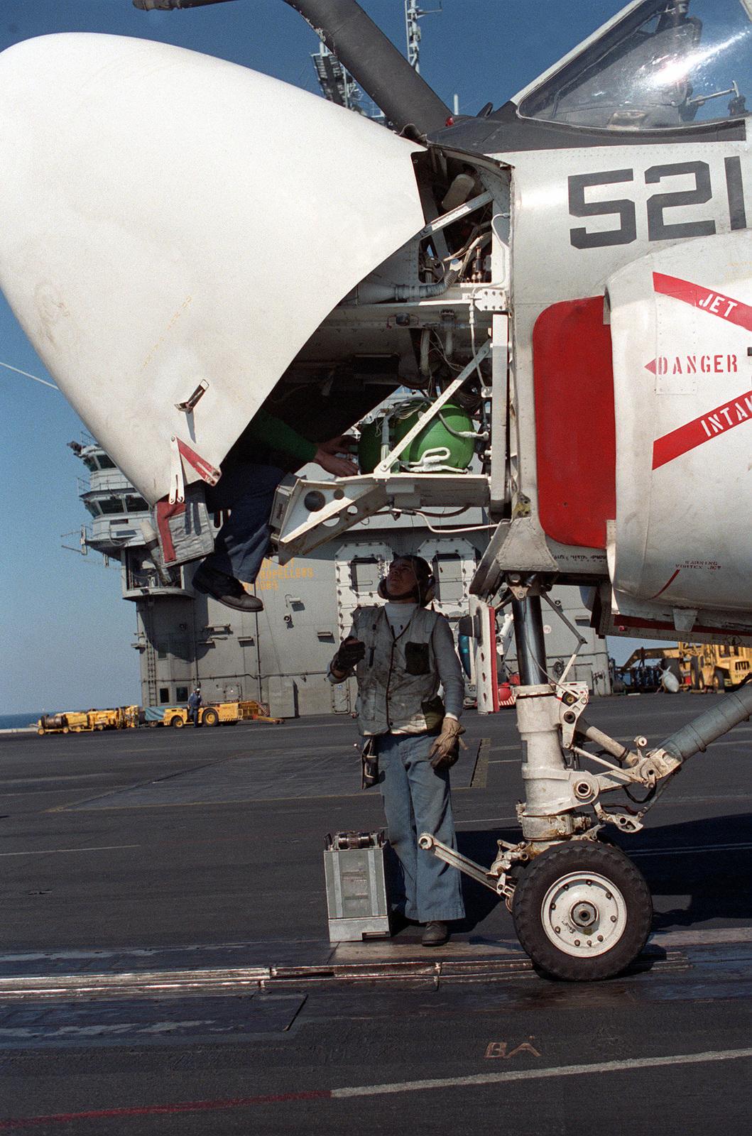 A maintenance crewman works under the nose of an Attack Squadron 34 (VA-34) A-6E Intruder aircraft on the flight deck of the nuclear-powered aircraft carrier USS DWIGHT D. EISENHOWER (CVN 69) during FLEET EX '90