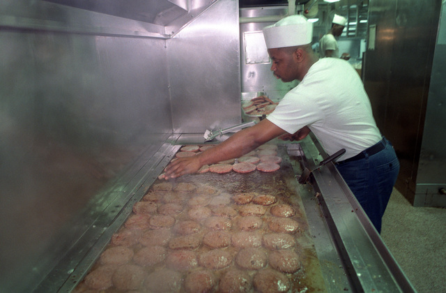 A mess management specialist cooks hamburger patties in the galley of one of the two enlisted mess decks aboard the nuclear-powered aircraft carrier USS DWIGHT D. EISENHOWER (CVN 69) during FLEET EX '90