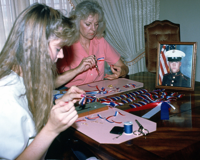 A photograph of Marine Sergeant Michael Zigabarra sits on a table near Diane and Nancy Zigabarra as they sew red, white and blue ribbons to show their support for the troops in the Persian Gulf region for Operation DESERT SHIELD
