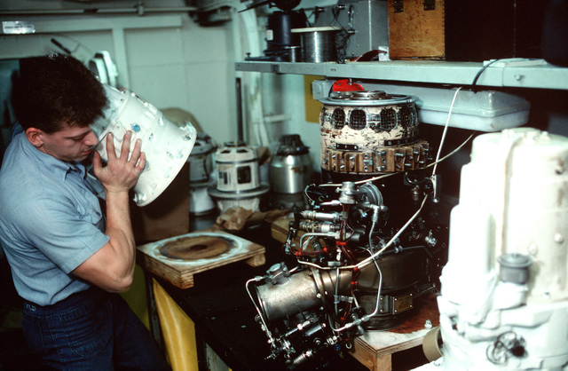 A sailor picks up a freshly painted piece of equipment in an Aircraft Intermediate Maintenance Department (AIMD) repair shop aboard the aircraft carrier USS JOHN F. KENNEDY (CV-67) during Fleet Ex 1-90