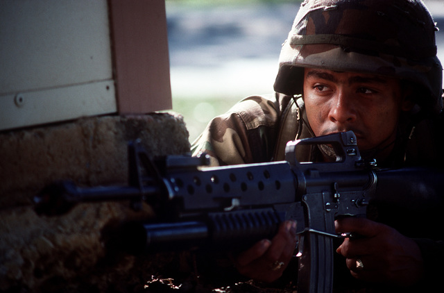 A soldier carrying an M-16A2 rifle equipped with an M-203 grenade launcher crouches at the base of a building during the joint service exercise Ocean Venture '90