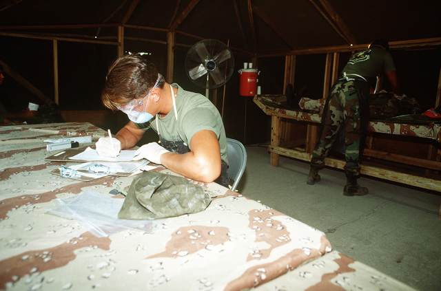 A team member completes paperwork on a simulated battlefield casualty as his companions remove personal effects and take photographs as part of the remains processing procedure. The exercise is taking place during the civil engineering/services competition Readiness Challenge '90
