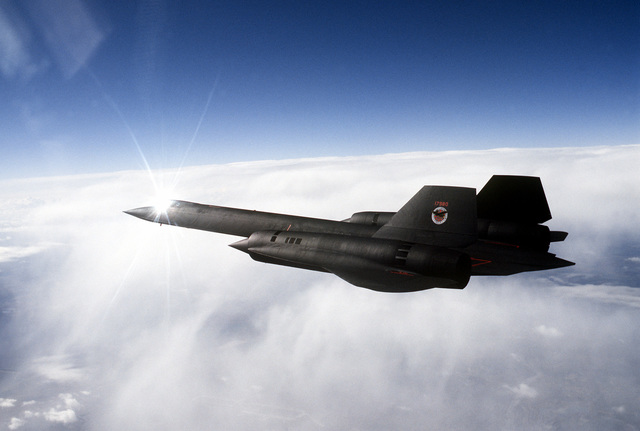 Air to air view left side view of a 9th Strategic Reconnaissance Wing's SR-71 Blackbird reconnaissance aircraft, flying over cloud cover, on a mission out of Beale Air Force Base, California. Exact Date Shot Unknown
