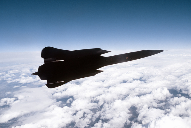 Air to air view right side view of a 9th Strategic Reconnaissance Wing's SR-71 Blackbird reconnaissance aircraft, as it banks left flying over scattered clouds, on a mission out of Beale Air Force Base, California. Exact Date Shot Unknown