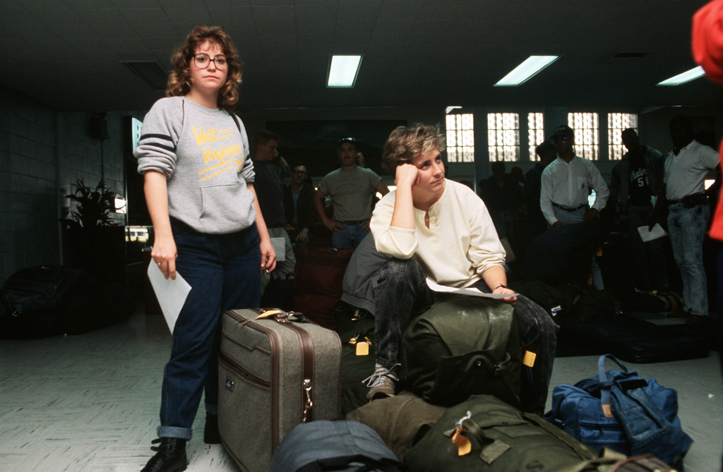 AMN Recruit Amy Estep and Aviation Machinist's Mate/AMN Susan McComb wait to have their baggage checked at the Military Airlift Command terminal, Clark Air Base. Travel restrictions were imposed on flights in and out of the Philippines due to a coup attempt on the government in Manila
