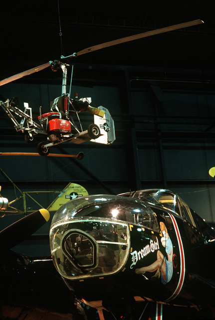 "An A-26 Invader aircraft dubbed ""Dream Girl"" stands on display beneath a gyrocopter at the Air Force Museum, the world's largest repository of aviation memorabilia"
