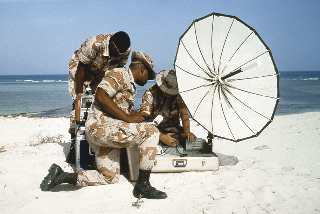 An Aerospace Audiovisual Service crew of videographers and photographers set up an Immarsat satellite transmitter on the sand during Operation DESERT STORM in Saudi Arabia. Exact Date Shot Unknown