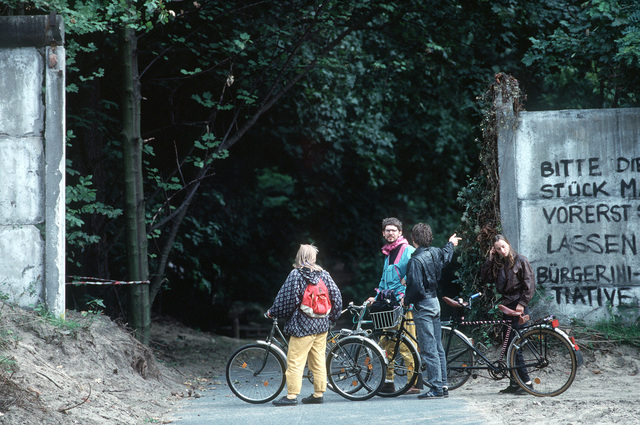Cyclists take a break near a remaining section of the Berlin Wall following Germany's reunification