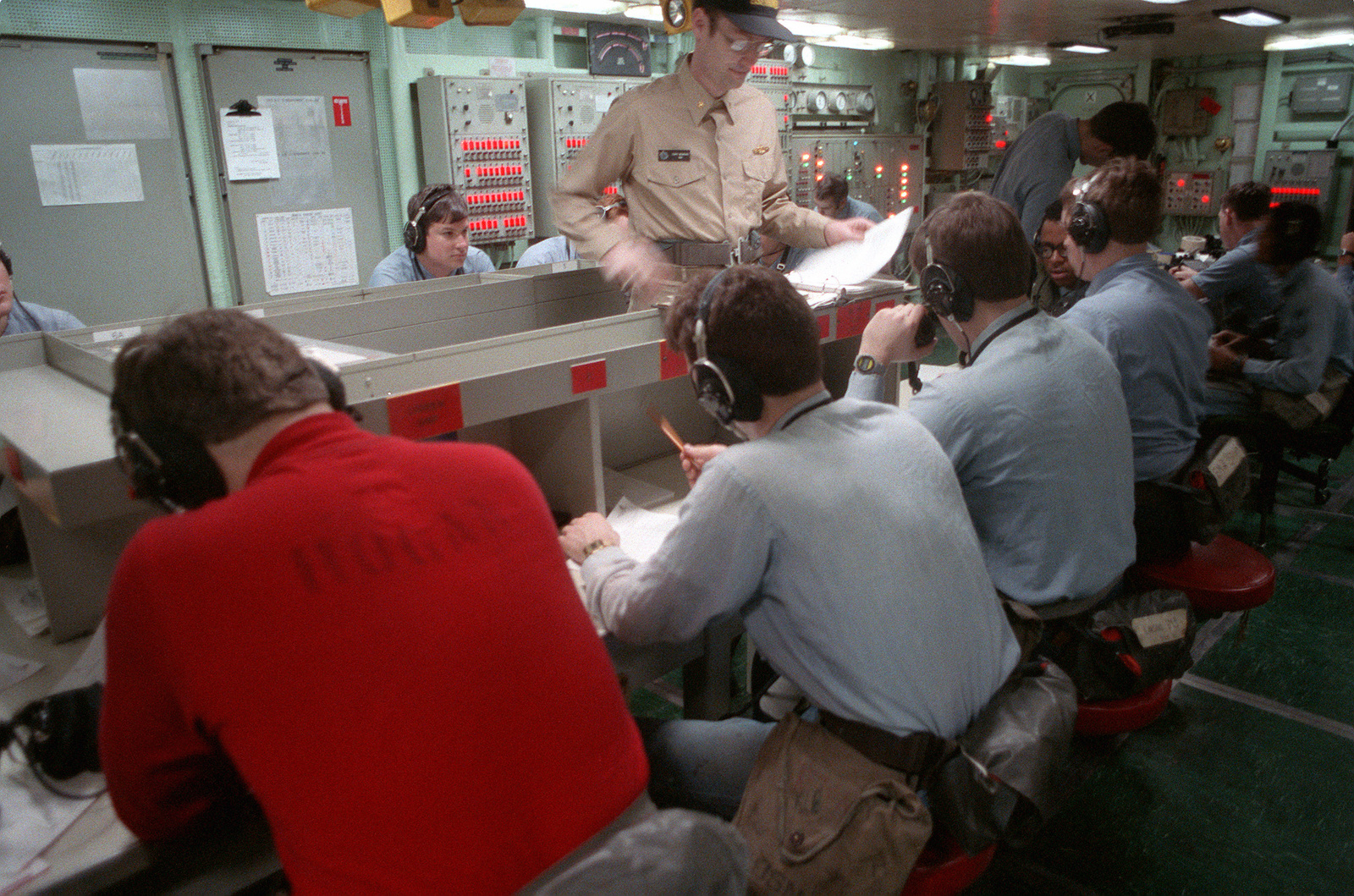 Damage control personnel monitor sound-powered telephones at their stations in damage control central during a general quarters drill aboard the nuclear-powered aircraft carrier USS DWIGHT D. EISENHOWER (CVN 69). The drill is taking place during FLEET EX '90