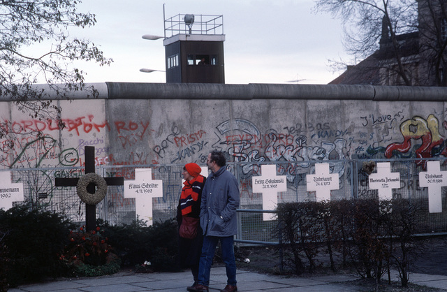 Following Germany's reunification, a couple reads grave markers of East Germans who died in an effort to escape over the Berlin Wall to the West