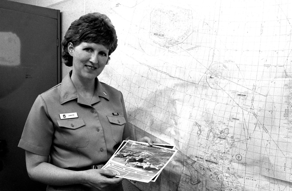 Lieutenant Junior Grade (LTJG) Laurie Rye, an intelligence officer assigned to Patrol Squadron 56 (VP-56) displays a stack of aircraft recognition training photographs