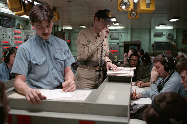 Lieutenant Steve Weingart, second from left, the damage control assistant aboard the nuclear-powered aircraft carrier USS DWIGHT D. EISENHOWER (CVN 69), coordinates damage control efforts from damage control central during a general quarters drill. At left is Hull Technician 2nd Class Jim Mason, the enlisted damage control assistant. The drill is taking place during FLEET EX '90