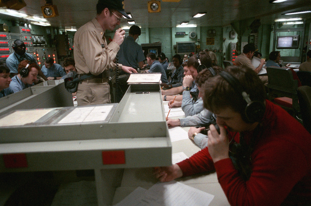 Lieutenant Steve Weingart, standing, the damage control assistant aboard the nuclear-powered aircraft carrier USS DWIGHT D. EISENHOWER (CVN 69), coordinates damage control efforts from damage control central during a general quarters drill. The drill is taking place during FLEET EX '90