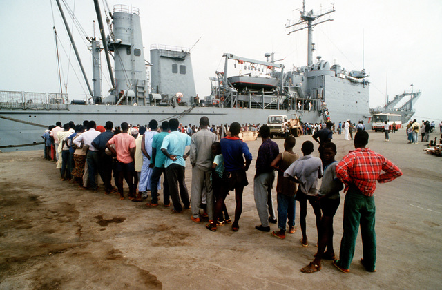 Local residents line up to see the tank landing ship USS BARNSTABLE COUNTY (LST-1197), during the vessel's port call. The BARNSTABLE COUNTY is visiting the port as part of its West Africa training cruise