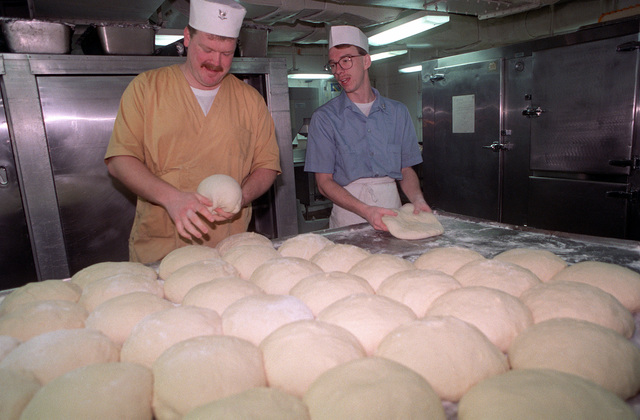 Mess management specialists knead bread and pizza dough in the bakery aboard the nuclear-powered aircraft carrier USS DWIGHT D. EISENHOWER (CVN 69) during FLEET EX '90