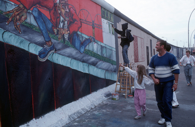 MSGT Tom Jenkins and daughter, Christina, stroll past a section of the Berlin Wall as an artist paints a mural following Germany's reunification