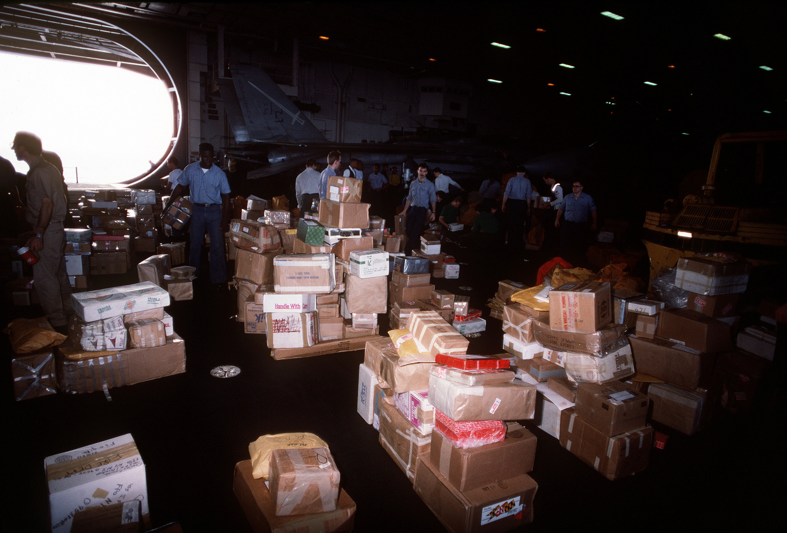 Postal clerks sort packages on the hangar deck aboard the aircraft carrier USS JOHN F. KENNEDY (CV-67) during Operation Desert Shield. Approximately 41,000 pounds of mail was received by the KENNEDY in this one shipment