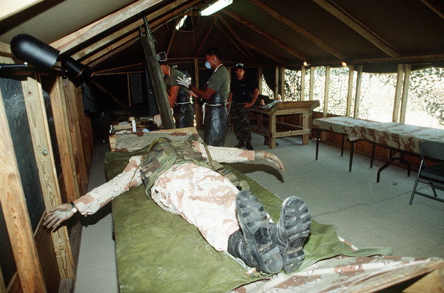 Team members prepare to work with a simulated battlefield casualty in the remains processing shelter during the civil engineering/services competition Readiness Challenge '90