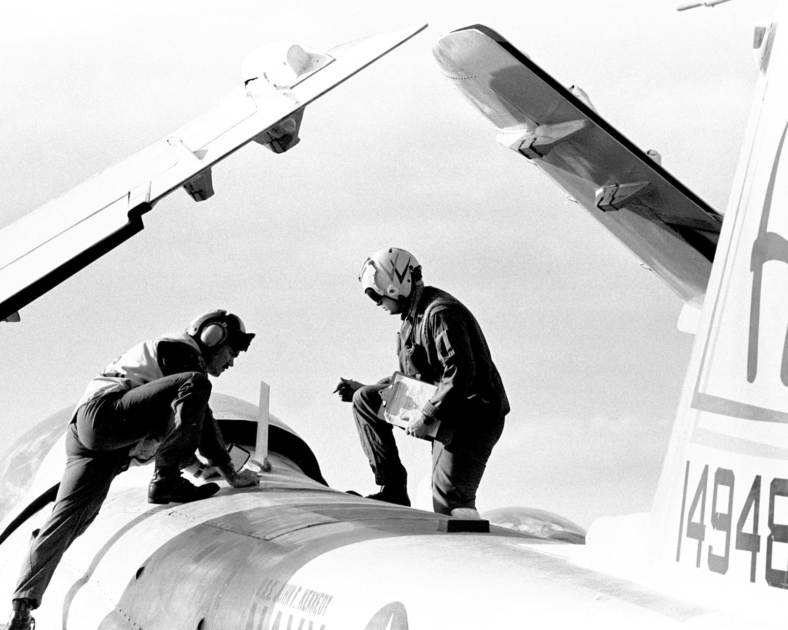 Two flight deck crew members inspect an A-6E Intruder aircraft aboard the aircraft carrier JOHN F. KENNEDY (CV-67) during FLEET EX 1-90