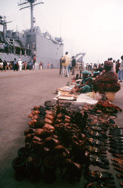 Vendors and their wares line the pier in the foreground as local residents tour the tank landing ship USS BARNSTABLE COUNTY (LST-1197), during its port call. The vessel is visiting the port as part of its West Africa training cruise