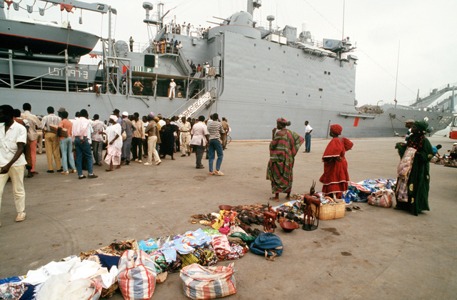 Vendor's and their wares line the pier in the foreground as local residents gather to see the tank landing ship USS BARNSTABLE COUNTY (LST-1197), during its port call. The vessel is visiting the port as part of its West Africa training cruise