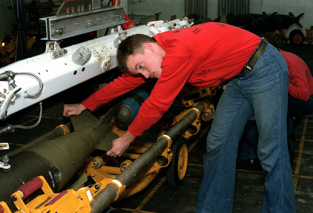 A weapons technician aboard the nuclear-powered aircraft carrier USS THEODORE ROOSEVELT (CVN-71) ensures that a BDU-45/B 500-pound practice bomb is securely attached to a weapons skid before additional ordnance is loaded