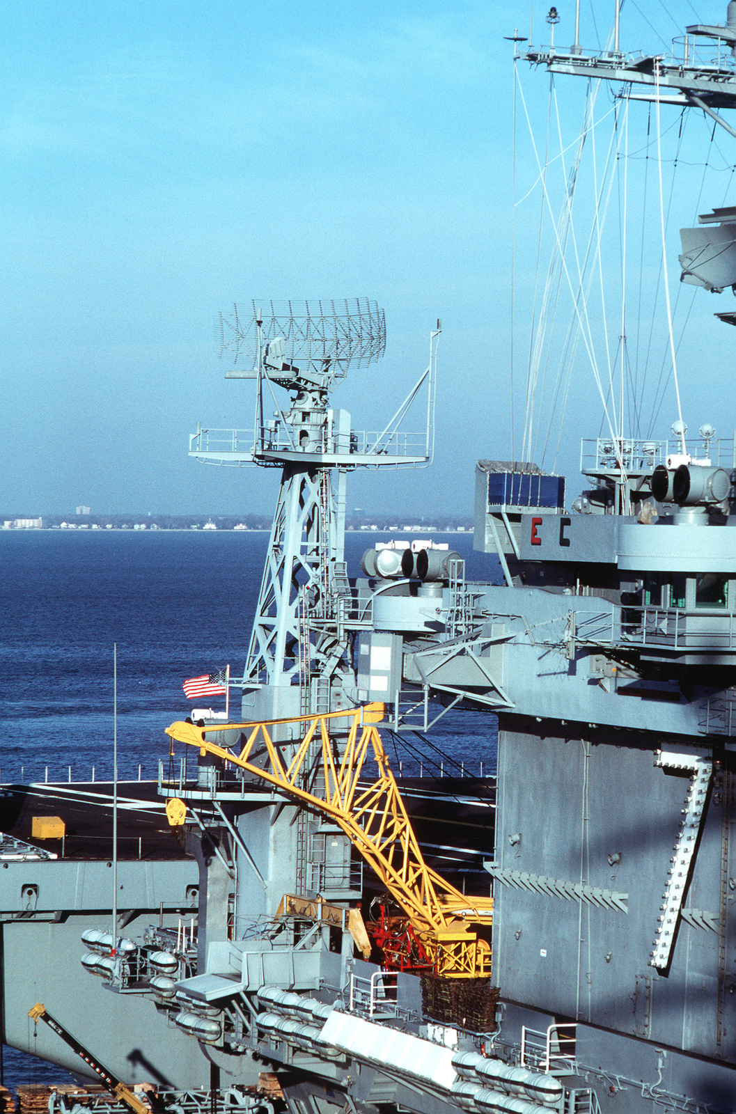 A view of the lattice mast behind the island of the nuclear-powered aircraft carrier USS THEODORE ROOSEVELT (CVN-71). The lattice mast supports the SPS-49 air search radar antenna
