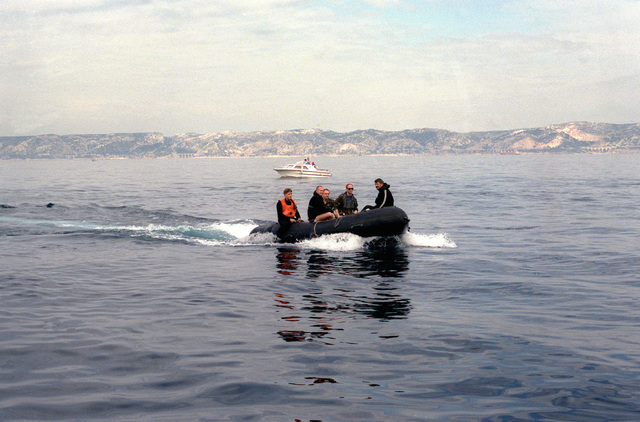 Members of a Navy explosive ordnance disposal team patrol a coastline in a Zodiac inflatable boat