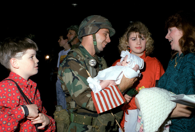 First Lieutenant Roberts of the 6th Infantry Regiment holds his dauther Lisa, who was born while Roberts was in Panama for Operation JUST CAUSE