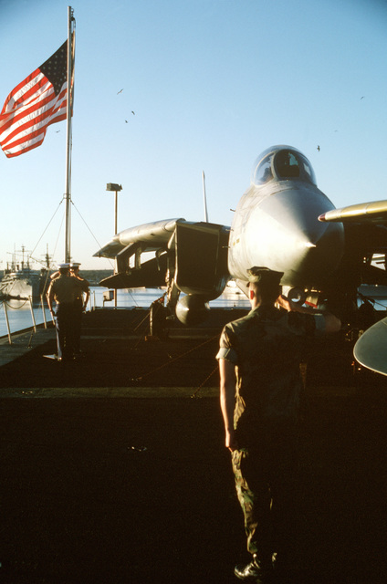 Lance Corporal Futo salutes as his fellow Marines, Lance Corporal Braddy and Lance Corporal Miranda, hoist the flag aboard the aircraft carrier USS JOHN F. KENNEDY (CV 67) at the beginning of FLEET EX-1-90. An F-14A Tomcat aircraft is in the background