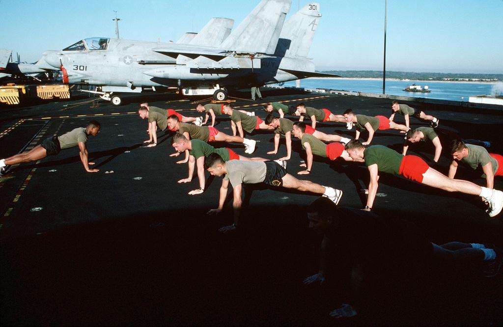 The U.S. Marine detachment aboard the aircraft carrier USS JOHN F. KENNEDY (CV-67) exercises on the flight deck beside an Attack Squadron 46 (VA-46) A-7E Corsair II aircraft during Fleet Ex 1-90