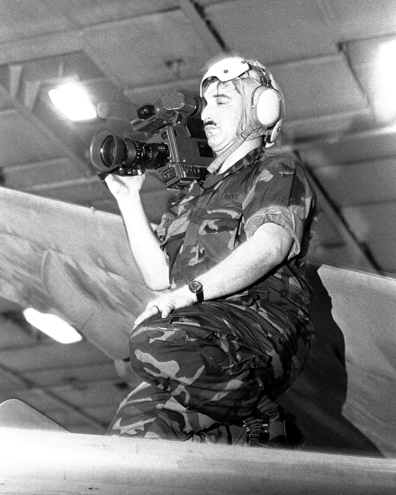 PH2 John Carnes, a member of Fleet Combat Camera Group Atlantic's motion picture crew, films a fire drill from atop an A-6 Intruder aircraft in the hangar bay of the aircraft carrier USS JOHN F. KENNEDY (CV-67) during FLEET EX 1-90