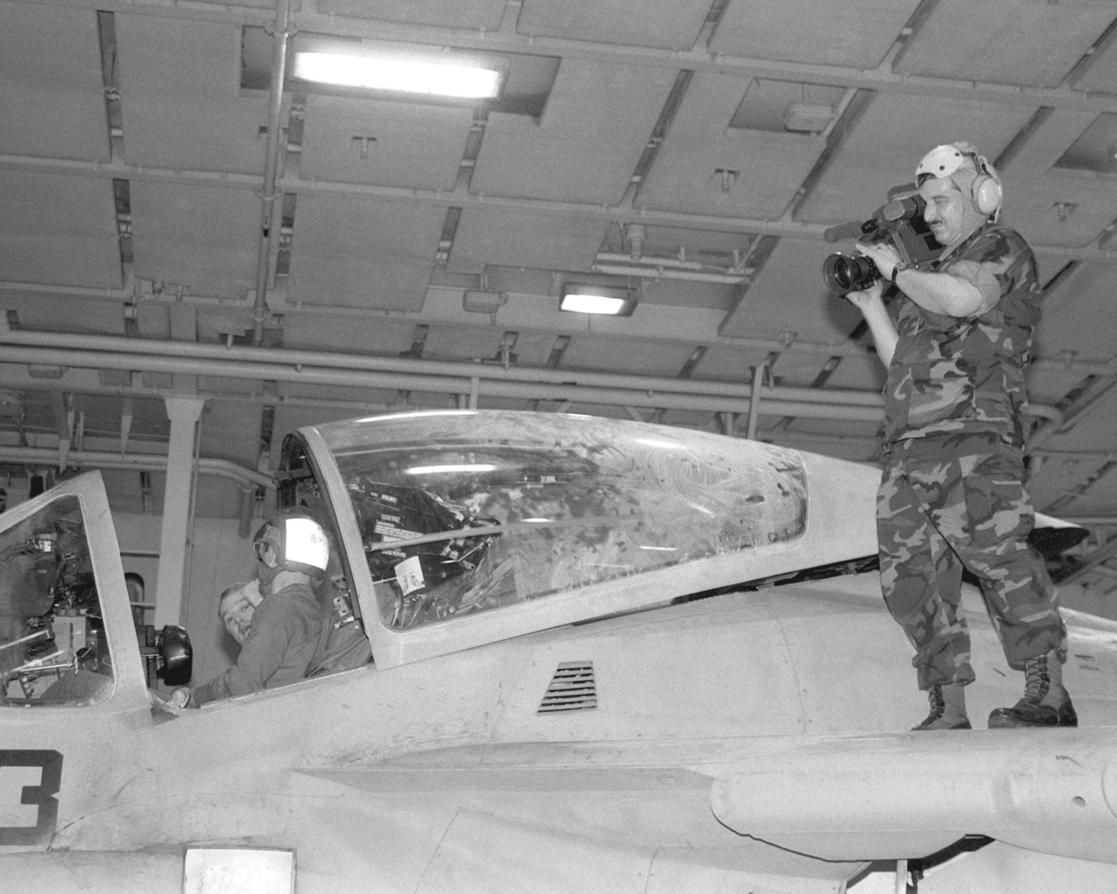 PH2 John Carnes stands on the wing of an Attack Squadron 75 (VA-75) A-6E Intruder aircraft to film a firefighting drill on the hangar deck of the aircraft carrier USS JOHN F. KENNEDY (CV-67) during FLEET EX 1-90