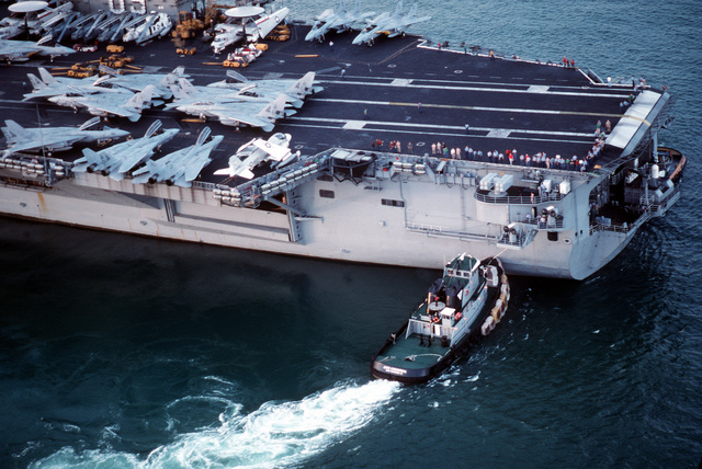 The commercial tug Cape Canaveral maneuvers the nuclear-powered aircraft carrier USS DWIGHT D. EISENHOWER (CVN-69) out of port as the vessel prepares to depart from Fort Lauderdale