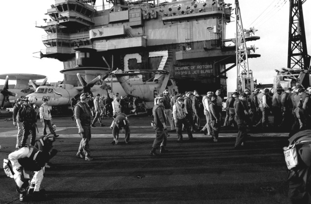 Dozens of crewmen walk slowly along the flight deck of the aircraft carrier USS JOHN F. KENNEDY (CV 67) as they search for debris that could cause foreign object damage (FOD) to aircraft operating on the ship. The KENNEDY is among the ships participating in FLEET EX 1-90