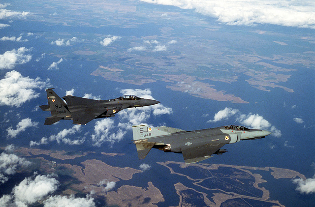 A 335th Tactical Fighter Squadron (335th TFS) F-4E Phantom II aircraft, foreground, and a 335th TFS F-15E Eagle aircraft fly over the coastline. The 335th TFS is converting from the Phantom to the F-15E