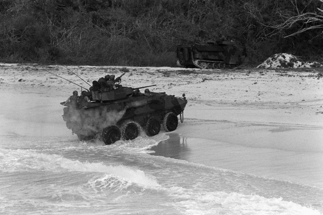 An LAV-25 light armored vehicle assigned to the 2nd Light Armored Infantry Battalion, 4th Marine Regiment, comes ashore during Fleet Ex 1-90. In the background is an AAVP-7 amphibious assault vehicle