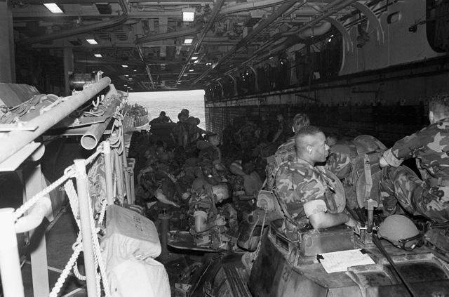 Marines of the 2nd Light Armored Infantry Battalion, 4th Marine Regiment, sit on their vehicles aboard a utility landing craft (LCU) in the well deck of the amphibious assault ship USS SAIPAN (LHA-2) during Fleet Ex 1-90