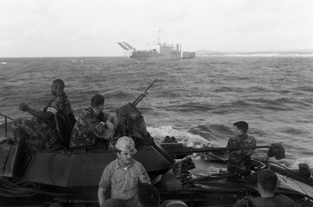 Marines of the 2nd Light Armored Infantry Battalion, 4th Marine Regiment, sit atop an LAV-25 light armored vehicle as they ride toward the beach at Vieques, Puerto Rico, aboard a utility landing craft (LCU) during Fleet Ex 1-90. The tank landing ship USS SUMTER (LST-1181) is in the background