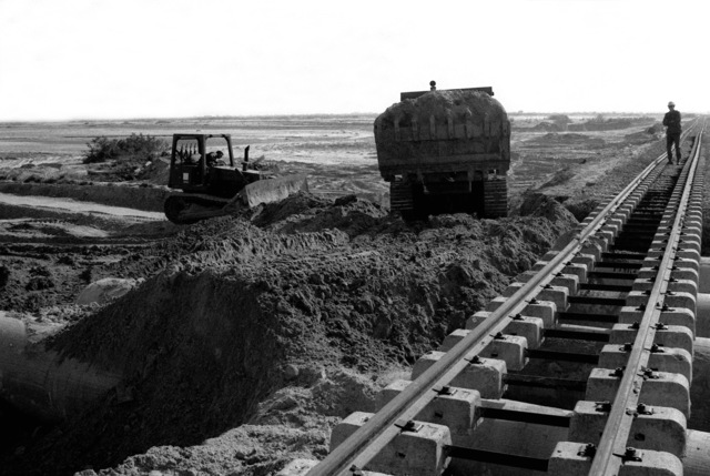 A crawler tractor prepares to deposit a load of backfill on top of cement culverts as US Navy Seabees work to repair a flood-damaged railroad during exercise ATLAS RAIL