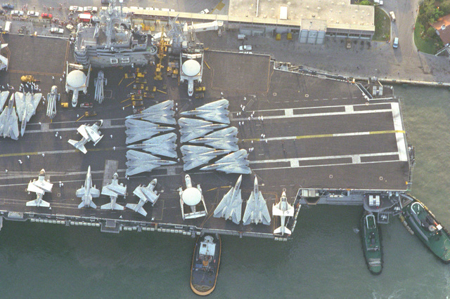 An overhead view of various aircraft parked on the deck of the nuclear-powered aircraft carrier USS Dwight D. Eisenhower (CVN-69) as large harbor tugs maneuver the vessel into port
