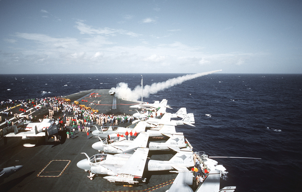 Crew members watch as a trainer missile is launched from a Mark 29 NATO Sea Sparrow launcher on the starboard bow of the nuclear-powered aircraft carrier USS ABRAHAM LINCOLN (CVN-72). Strike Fighter Squadron 15 (VFA-15) F/A-18 Hornet aircraft and A-6E Intruder aircraft are parked on the flight deck