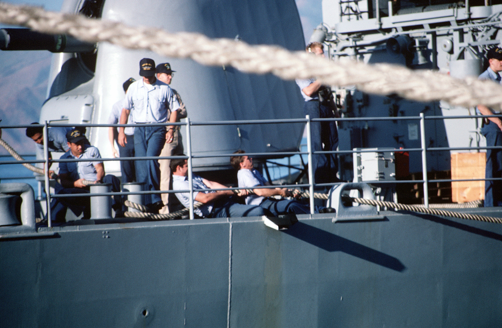 Sailors aboard the destroyer USS HEWITT (DD 966) haul in on a line as the ship is tied up alongside another vessel
