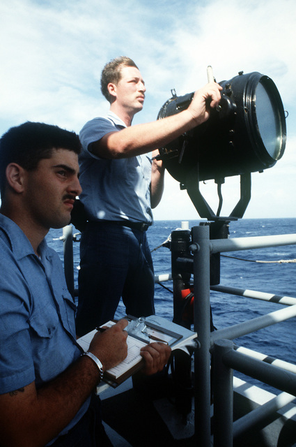 Sailors on the guided missile frigate USS CLARK (FFG-11) man a signal lantern and note pad as they prepare to send a message and record the response. Under Coast Guard command, Clark and a Naval Air Reserve helicopter detachment are on a drug-smuggling interdiction patrol