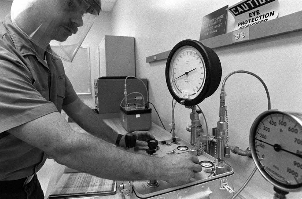 SEAMAN Recruit Ken Fulmer tests the accuracy of a high pressure gauge at the Opticalmen and Instrumentmen School