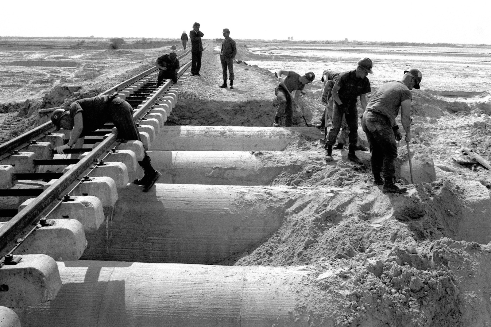 US Navy Seabees shovel backfill over cement culverts as they repair a flood-damaged railroad during exercise ATLAS RAIL