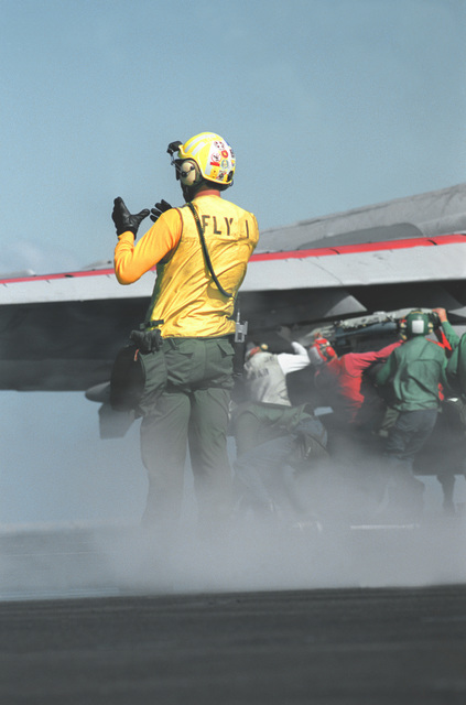 A plane director guides an aircraft into place on the No. 1 catapult aboard the nuclear-powered aircraft carrier USS ABRAHAM LINCOLN (CVN-72) during the ship's shakedown cruise