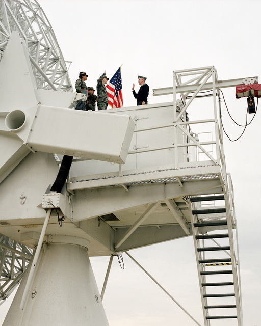 COL Styer administers the re-enlistment oath to SSGT Jerry Johnson as they stand atop a shelter on an OE-222 antenna