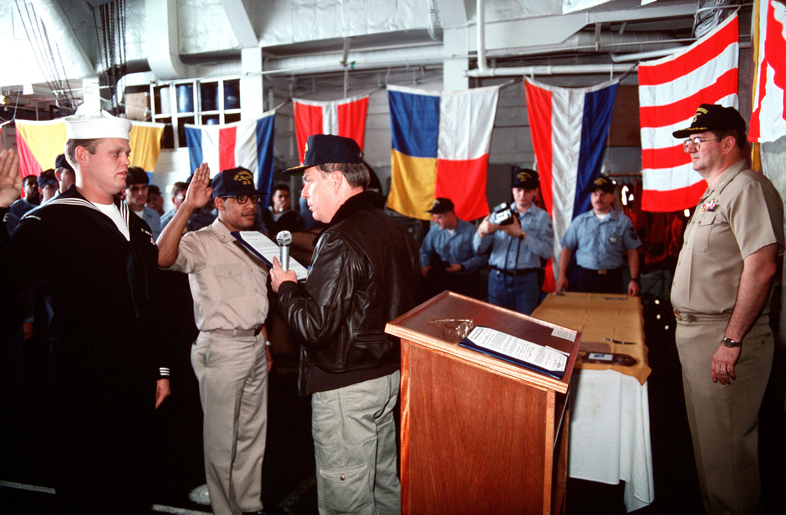 Secretary of the Navy H. Lawrence Garrett III, administers the oath of reenlistment to a pair of enlisted men while visiting the guided missile cruiser USS TICONDEROGA (CG-47) during Fleet Ex 1-90. CAPT Morris C. Foote, the TICONDEROGA's Commanding Officer, is at right