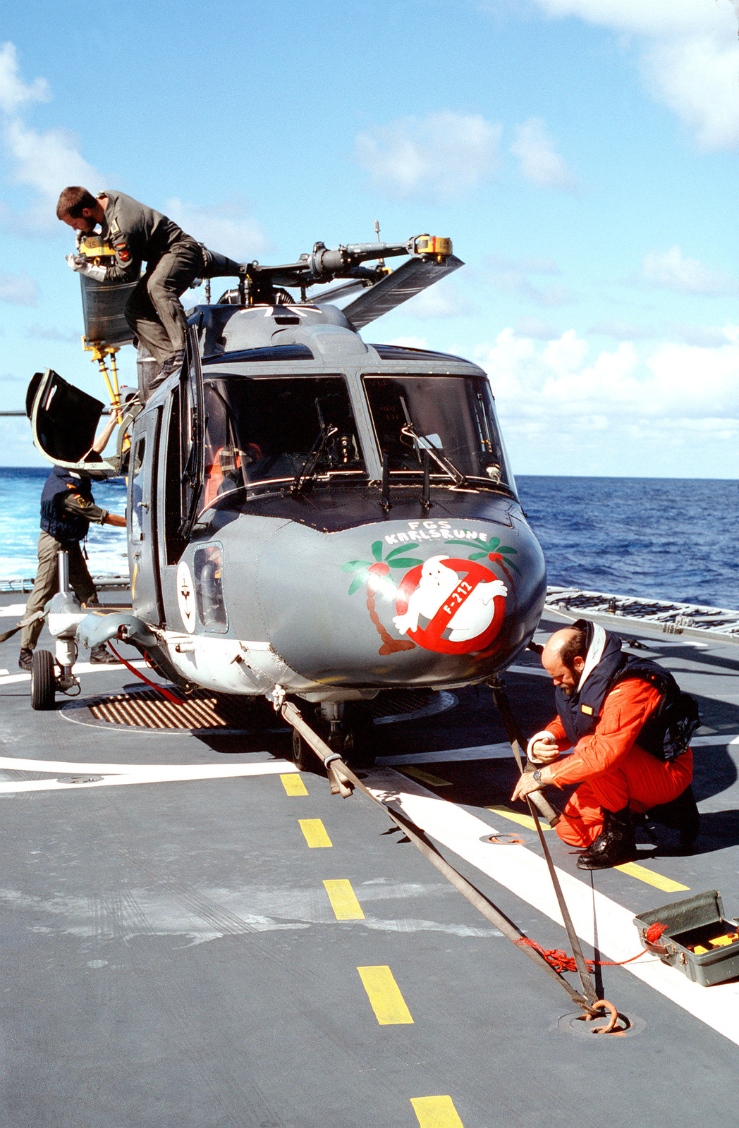 Fgs Security a crewman checks a tie-down strap as two others secure the